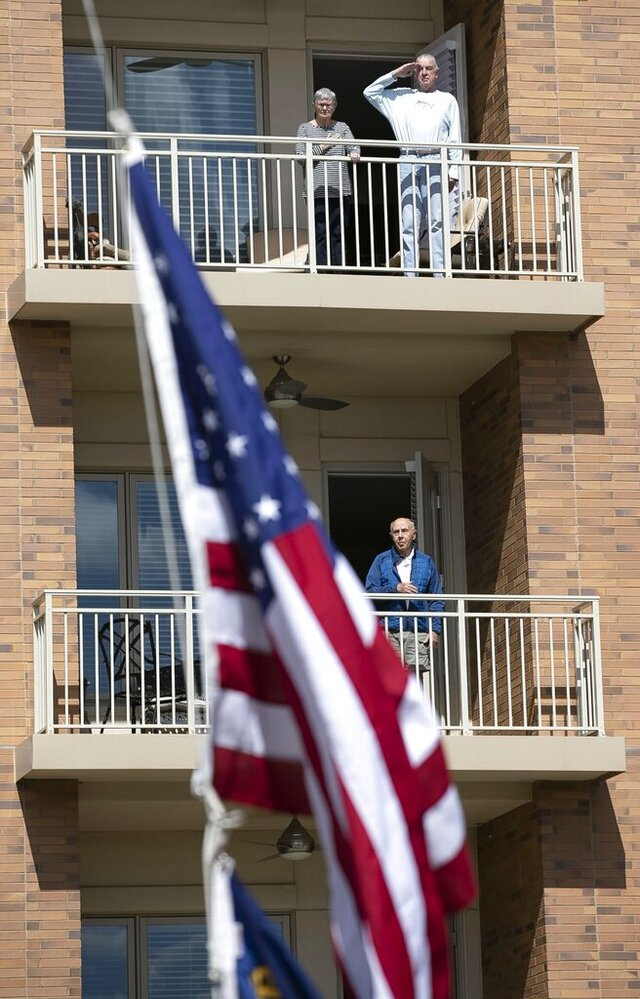 Vietnam veteran John Durfee salutes the American Flag from his balcony as it raised in the courtyard on Thursday, April 2, 2020 at The Cardinal at North Hills in Raleigh, N.C. Durfee's wife Patricia joins him as do other neighboring residents for their morning ritual, staying in their homes now to practice social distancing. (Robert Willett/The News & Observer via AP)