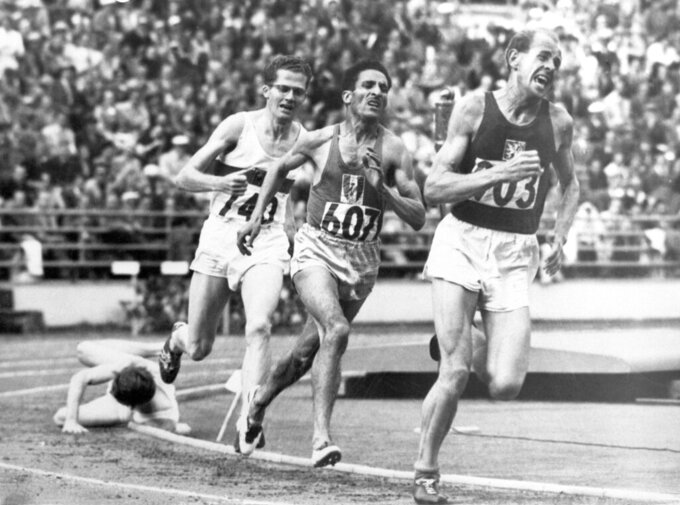 "FILE - In this July 24, 1952, file photo, British athlete Christopher ""Chris"" Chataway falls as Emil Zatopek of Czechoslovakia, followed by Alain Mimoun of France and German bronze medal winner Herbert Schade, leads near the end of the Men's final 5000 meter race at the Summer Olympic Games on in Helsinki, Finland. (AP Photo/File)"