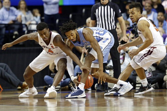 Virginia Tech guard Nahiem Alleyne (4) and guard Wabissa Bede, right, chase the ball with North Carolina guard Leaky Black during the first half of an NCAA college basketball game at the Atlantic Coast Conference tournament in Greensboro, N.C., Tuesday, March 10, 2020. (AP Photo/Gerry Broome)