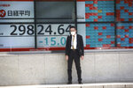 A man stands in front of an electronic stock board of a securities firm in Tokyo, Wednesday, Sept. 22, 2021. Asian shares were mostly lower on Wednesday after major indexes ended mixed on Wall Street. (AP Photo/Koji Sasahara)