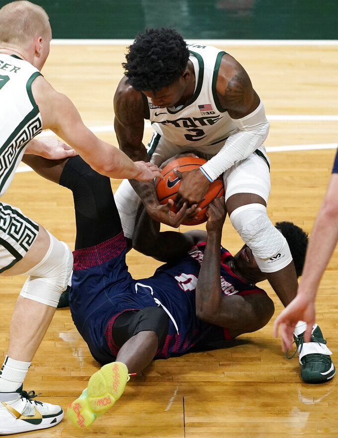 Michigan State guard Rocket Watts (2) and Detroit Mercy guard Antoine Davis (0) try to control the ball during the second half of an NCAA college basketball game Friday, Dec. 4, 2020, in East Lansing, Mich. (AP Photo/Carlos Osorio)