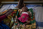 """FILE - In this Tuesday, May 11, 2021 file photo, Abeba Gebru, 37, from the village of Getskimilesley, sits with her malnourished daughter, Tigsti Mahderekal, 20 days old, in the treatment tent of a medical clinic in the town of Abi Adi, in the Tigray region of northern Ethiopia. Pope Francis demanded Sunday, June 13, 2021 at his noon blessing that humanitarian aid reach hungry people in the war-torn Tigray region who have been """"struck by a grave humanitarian crisis that has exposed the poorest to famine"""" and called for an immediate end to the fighting. (AP Photo/Ben Curtis, File)"""
