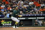 Oakland Athletics' Khris Davis hits an RBI single against the Houston Astros during the first inning of a baseball game Tuesday, Sept. 10, 2019, in Houston. (AP Photo/David J. Phillip)