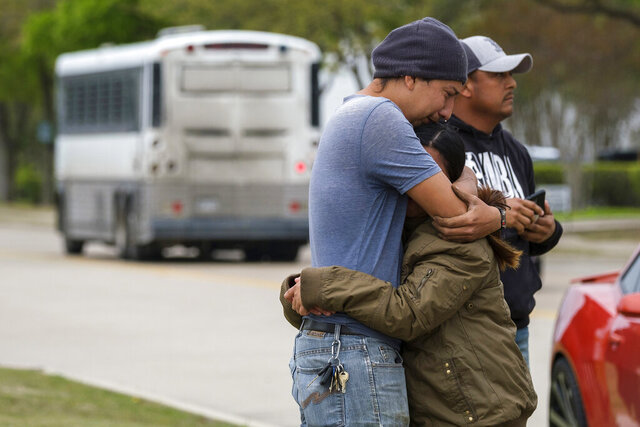 FILE - In this April 3, 2019, file photo, a couple who did not want to give their names embrace outside CVE Group as a bus from LaSalle Corrections Transport departs with detained workers after a raid by U.S. Immigration and Customs Enforcement in Allen, Texas. The ACLU of Texas has filed a federal lawsuit against U.S. Immigration and Customs Enforcement over the April 2019, raid of the business in the Dallas suburb. (Smiley N. Pool/The Dallas Morning News via AP, File)