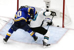 San Jose Sharks center Logan Couture (39) scores the tying goal against St. Louis Blues center Ryan O'Reilly (90) and Jordan Binnington during the third period in Game 3 of the NHL hockey Stanley Cup Western Conference final series Wednesday, May 15, 2019, in St. Louis. The goal sent the game into overtime. (AP Photo/Jeff Roberson)