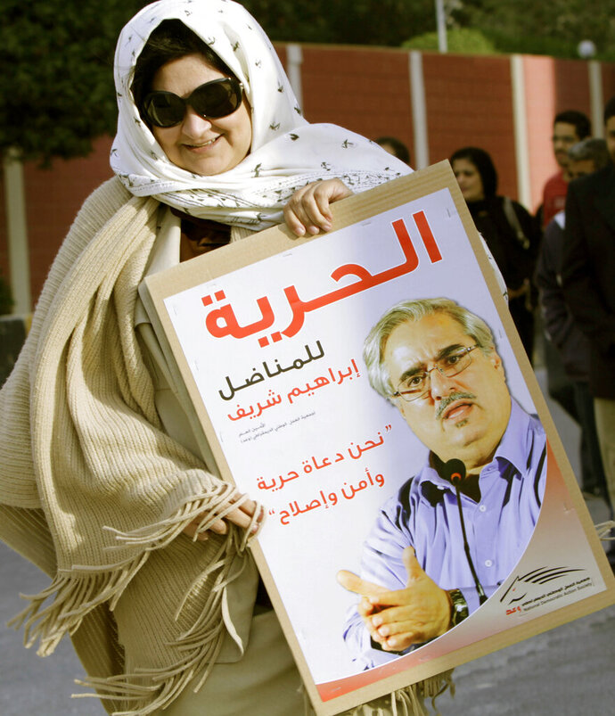 FILE - In this Feb. 22, 2012 file photo, Fareeda Ghulam, the wife of Bahrain opposition politician Ebrahim Sharif, carries a poster with her husband's image as she arrives for an anti-government rally outside the offices of the United Nations in Manama, Bahrain. Activists said Wednesday, March 13, 2019, that Sharif now faces up to six months in prison for a tweet about Sudanese President Omar al-Bashir. Poster reads,