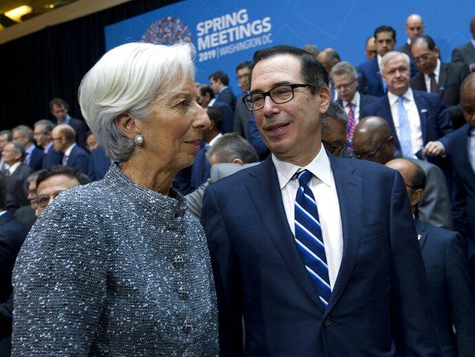 International Monetary Fund (IMF) Managing Director Christine Lagarde speaks with Treasury Secretary Steven Mnuchin during the International Monetary Fund IMF Governors group photo at the World Bank/IMF Spring Meetings in Washington, Saturday, April 13, 2019. (AP Photo/Jose Luis Magana)