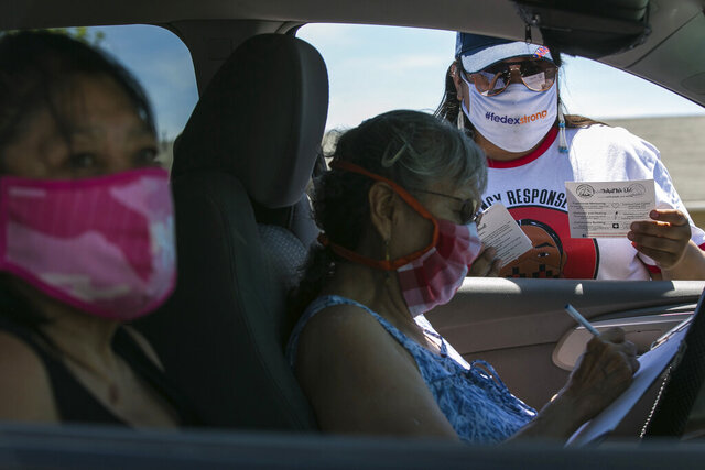 In this photo taken on Friday, June 26, 2020, Natasha Scott, right, provides flyer information about the Peacekeeper Society to Patricia Randall, center, and Floraine Gardee, left, during a drive-thru distribution of food and emergency supplies at Harrah City Hall in Harrah, Wash., during the coronavirus pandemic. (Amanda Ray/Yakima Herald-Republic via AP)