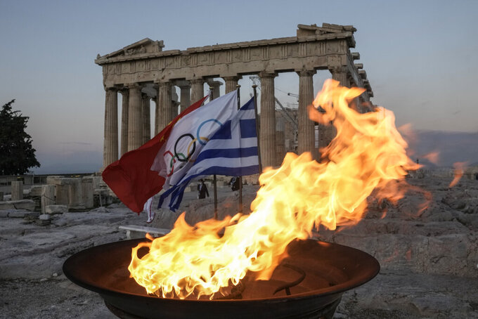 The Olympic Flame burns at the cauldron in front of ancient Parthenon temple atop of the Acropolis hill in Athens, Tuesday, Oct. 19, 2021. The flame will be transported by torch relay to Beijing, China, which will host the Feb. 4-20, 2022 Winter Olympics.(AP Photo/Petros Giannakouris)