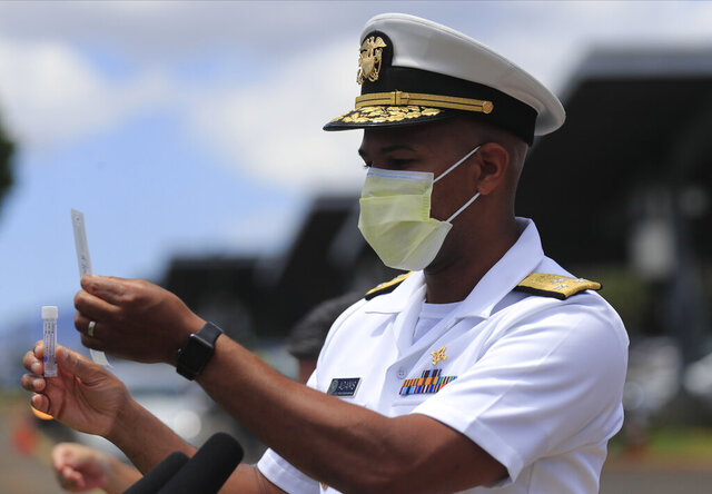 U.S. Surgeon General Jerome Adams demonstrates the self-administered COVID-19 swab test on Wednesday, Aug. 26, 2020 at Leeward Community College in Pearl City, Hawaii. According to a criminal complaint filed in court, U.S. Surgeon General Jerome Adams was cited for being in a closed Hawaii park. At the time of the August citation, Adams was in Hawaii helping with surge-testing efforts amid a spike in COVID-19 cases. (Jamm Aquino/Honolulu Star-Advertiser via AP)