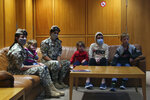 Members of the Lebanese General Security forces sit with Albanian children during an operation to take them back home to Albania from al-Hol, northern Syria, at the Rafik Hariri International Airport in Beirut, Lebanon, Tuesday, Oct. 27, 2020. The repatriation of four children and a woman related to Albanian nationals who joined Islamic extremist groups in Syria