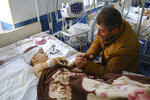 A man speaks with his child, wounded during shelling, in Stepanakert, the self-proclaimed Republic of Nagorno-Karabakh, Azerbaijan, Monday, Sept. 28, 2020. Fighting between Armenian and Azerbaijani forces over the disputed separatist region of Nagorno-Karabakh continued on Monday morning after erupting the day before, with both sides blaming each other for resuming the attacks. (Areg Balayan/PAN Photo via AP)
