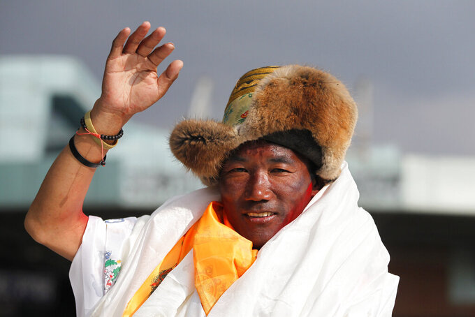 FILE - In this May 20, 2018, file photo, Nepalese veteran Sherpa guide, Kami Rita waves as he arrives in Kathmandu, Nepal. Rita, 51, an ace Sherpa guide scaled Mount Everest Friday for the 25th time breaking his own record for the most successful ascents of the world's highest peak.  (AP Photo/Niranjan Shrestha, File)
