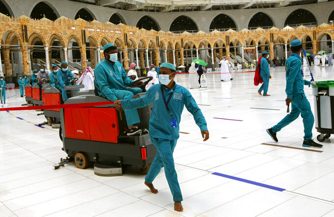 Workers disinfect the grounds at the Grand Mosque to help protect against the coronavirus in the Muslim holy city of Mecca, Saudi Arabia, Thursday, July 22, 2021. The virus has taken its toll on the annual hajj for a second year running. What once drew some 2.5 million Muslims from all walks of life from across the globe, the hajj pilgrimage is now almost unrecognizable in scale. (AP Photo/Amr Nabil)
