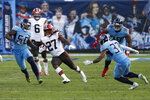 Cleveland Browns running back Kareem Hunt (27) tries to get past Tennessee Titans defenders Derick Roberson (50) and Amani Hooker (37) in the second half of an NFL football game Sunday, Dec. 6, 2020, in Nashville, Tenn. (AP Photo/Wade Payne)
