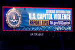 A billboard seeking tips about rioters who breached the United States Capitol Building on Jan. 6 stands along Interstate 35 Saturday, Jan. 16, 2021, in Kansas City, Kan. (AP Photo/Charlie Riedel)
