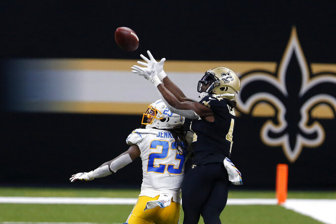 New Orleans Saints running back Alvin Kamara (41) pulls in a pass over Los Angeles Chargers strong safety Rayshawn Jenkins (23), setting up a touchdown, in the second half of an NFL football game in New Orleans, Monday, Oct. 12, 2020. The Saints won in overtime, 30-27. (AP Photo/Brett Duke)