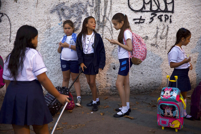 In this Feb. 4, 2019 photo, students arrive for their first day of school, in Rio de Janeiro, Brazil. Brazilian President Jair Bolsonaro is taking his anti-leftist ideological war to the country's classrooms and universities, causing angst among teachers and education officials who say the government wants to fight an enemy that doesn't exist. (AP Photo/Silvia Izquierdo)