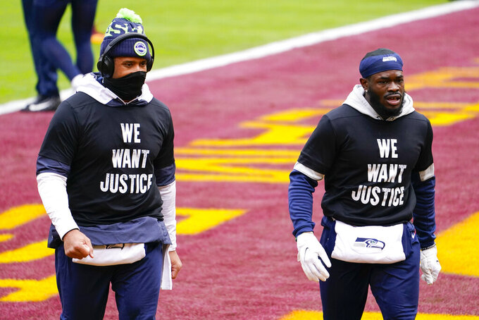 Seattle Seahawks quarterback Russell Wilson (3), left, walking on the field with teammate wide receiver Penny Hart (19) on the field before the start of an NFL football game against the Washington Football Team, Sunday, Dec. 20, 2020, in Landover, Md. (AP Photo/Andrew Harnik)