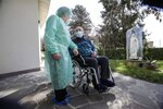 Palmiro Tami, 82, holds hand with his wife Franca Persico in the garden of the Fondazione Martino Zanchi nursing home, after receiving the second shot of Moderna COVID-19 Vaccine, in Alzano Lombardo, northern Italy, Monday, March 22, 2021. Italy's nursing homes have been declared an initial success in an otherwise lagging vaccine campaign. At a nursing home near Bergamo, one 82-year-old resident received his second jab, and a surprise visit from his 77-year-old wife. Their last hug had been through plastic on his birthday, in February. (AP Photo/Luca Bruno)