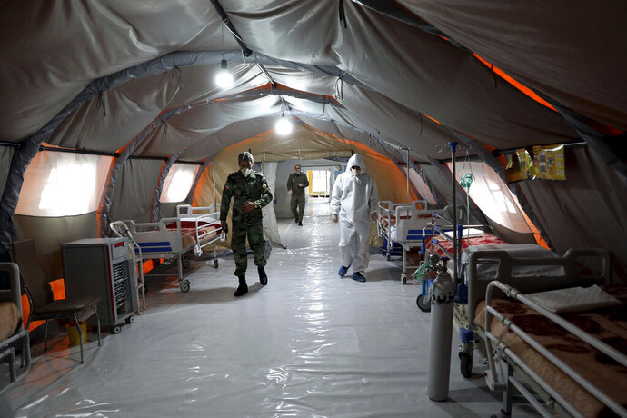 FILE - In this March 26, 2020 file photo, Iranian army soldiers work in a temporary 2,000-bed hospital for coronavirus patients set up by the army at the International Exhibition Center in northern Tehran, Iran. Dozens of medical staffers have died of COVID-19 in Iran. Doctors and nurses and other staffers have been hard hit. During the first 90 days of the virus outbreak alone, about one medical staffer died each day. (AP Photo/Ebrahim Noroozi, File)