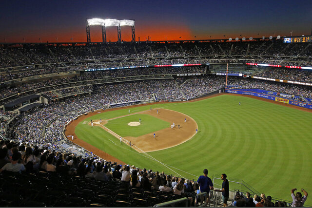 FILE - In this Aug. 29, 2019, file photo, the sun sets behind Citi Field during a baseball game between the New York Mets and the Chicago Cubs in New York. Major League Baseball players ignored claims by clubs that they need to take additional pay cuts, instead proposing they receive a far higher percentage of salaries and a commit to a longer schedule as part of a counteroffer to start the coronavirus-delayed season. (AP Photo/Kathy Willens, File)