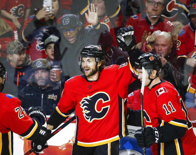 Calgary Flames' Michael Frolik, left, of the Czech Republic, celebrates his goal with teammate Mikael Backlund, of Sweden, during third period NHL hockey action against the Arizona Coyotes in Calgary, Alberta, Monday, Feb. 18, 2019. (Jeff McIntosh/The Canadian Press via AP)