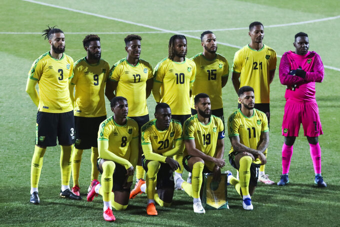 Jamaica players stand during the national anthem prior the international friendly soccer match between USA and Jamaica at SC Wiener Neustadt stadium in Wiener Neustadt, Austria, Thursday, March 25, 2021. (AP Photo/Ronald Zak)
