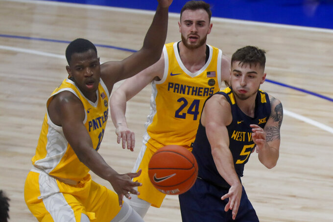 West Virginia's Jordan McCabe (5) passes as Pittsburgh's Abdoul Karim Coulibaly (12) and Ryan Murphy (24) defend during the second half of an NCAA college basketball game, Friday, Nov. 15, 2019, in Pittsburgh. (AP Photo/Keith Srakocic)