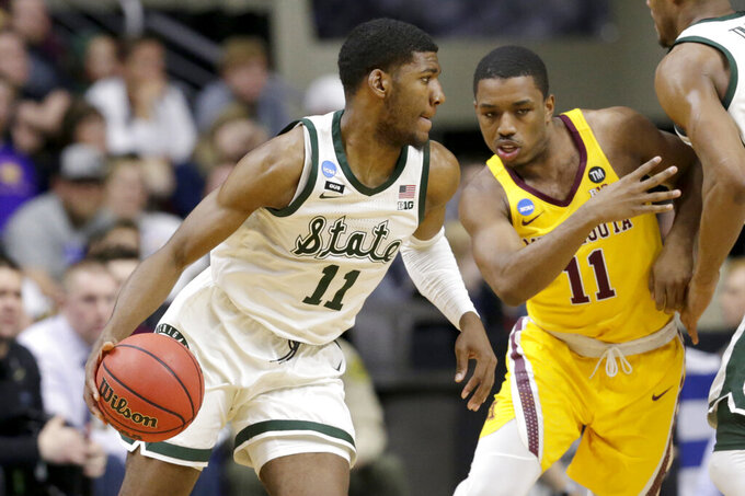 Michigan State's Aaron Henry (11) tries to drive around Minnesota's Isaiah Washington, right, during the first half of a second round men's college basketball game in the NCAA Tournament, in Des Moines, Iowa, Saturday, March 23, 2019. (AP Photo/Nati Harnik)