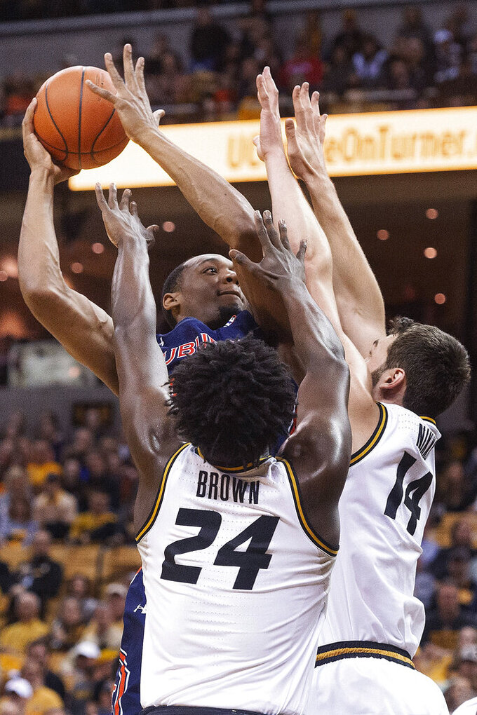 Auburn's Austin Wiley, top, shoots over Missouri's Reed Nikko, right, and Kobe Brown during the first half of an NCAA college basketball game Saturday, Feb. 15, 2020, in Columbia, Mo. (AP Photo/L.G. Patterson)