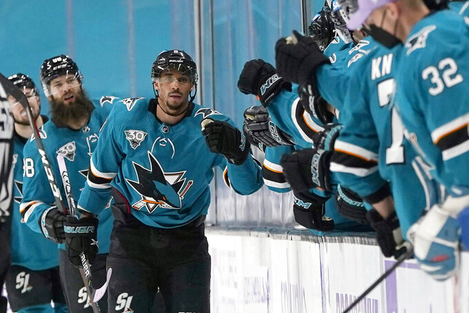 FILE - In this Monday, May 3, 2021, file photo, San Jose Sharks left wing Evander Kane, middle, is congratulated by teammates after scoring against the Colorado Avalanche during the second period of an NHL hockey game in San Jose, Calif. The NHL suspending San Jose's Evander Kane 21 games for submitting a fake vaccination card and Washington State firing football coach Nick Rolovich for failing to comply with a vaccine mandate Monday provided two more reminders of the impact the coronavirus is still having on professional and college sports. (AP Photo/Jeff Chiu, File)