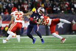 Kansas City Chiefs safeties Tyrann Mathieu, left, and Juan Thornhill, right, pursue New England Patriots wide receiver Julian Edelman after a catch in the first half of an NFL football game, Sunday, Dec. 8, 2019, in Foxborough, Mass. (AP Photo/Elise Amendola)