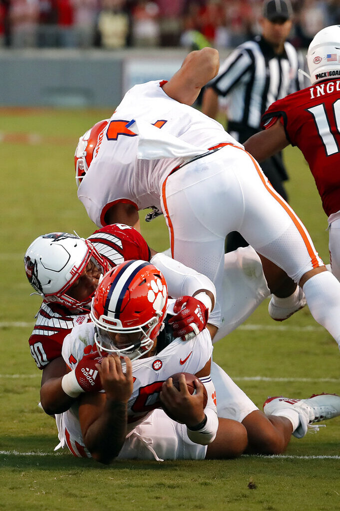 North Carolina State's Savion Jackson (90) tackles Clemson's D.J. Uiagalelei (5) as the left leg of Clemson running back Will Shipley (1) gets caught with North Carolina State's Tanner Ingle (10) nearby during the second half of an NCAA college football game in Raleigh, N.C., Saturday, Sept. 25, 2021. (AP Photo/Karl B DeBlaker)