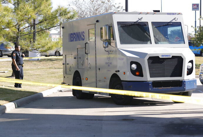 Law enforcement investigate the scene after two men attempted to rob a Brinks security armored truck at a bank Tuesday, Nov. 19, 2019, in Willis, Texas. Authorities say a guard fatally shot a person suspected of trying to rob the armored truck at a bank north of Houston and another suspect remains on the run. (Jason Fochtman/Houston Chronicle via AP)