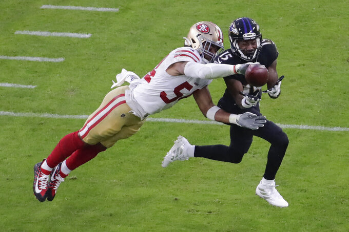 San Francisco 49ers middle linebacker Fred Warner (54) blocks Baltimore Ravens wide receiver Marquise Brown (15) from catching the ball during the first half of an NFL football game, Sunday, Dec. 1, 2019, in Baltimore, Md. (AP Photo/Julio Cortez)
