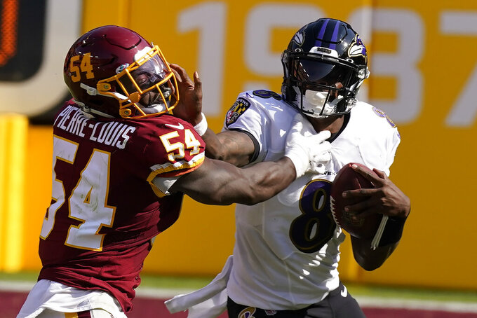 Washington Football Team outside linebacker Kevin Pierre-Louis (54) hits Baltimore Ravens quarterback Lamar Jackson (8) during the second half of an NFL football game, Sunday, Oct. 4, 2020, in Landover, Md. (AP Photo/Steve Helber)