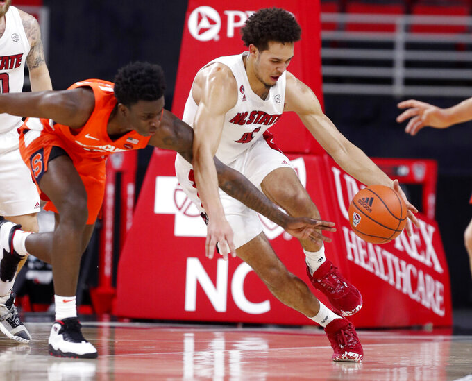 North Carolina State's Jericole Hellems (4) brings the ball past Syracuse's Kadary Richmond (3) during the first half of an NCAA college basketball game, Tuesday, Feb. 9, 2021 in Raleigh, N.C. (Ethan Hyman/The News & Observer via AP, Pool)