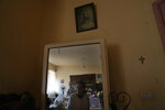 Marie Orfali, 76, is reflected in a mirror under a picture of Jesus in her apartment in Beirut, Lebanon, Tuesday, June 15, 2021. Tiny and bowed by age, Marie Orfali makes the trip five times a week from her Beirut apartment to the local church, a charity and a nearby soup kitchen to fetch a cooked meal for her and her 84-year-old husband, Raymond. (AP Photo/Hassan Ammar)