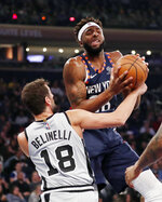 San Antonio Spurs guard Marco Belinelli (18) tries to strip the ball from New York Knicks center Mitchell Robinson (26) during the first half of an NBA basketball game in New York, Sunday, Feb. 24, 2019. (AP Photo/Kathy Willens)