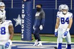 Dallas Cowboys' Ezekiel Elliott, center, watches as the team warms up for an NFL football game against the San Francisco 49ers in Arlington, Texas, Sunday, Dec. 20, 2020. Elliott is recovering from a calf injury. (AP Photo/Michael Ainsworth)