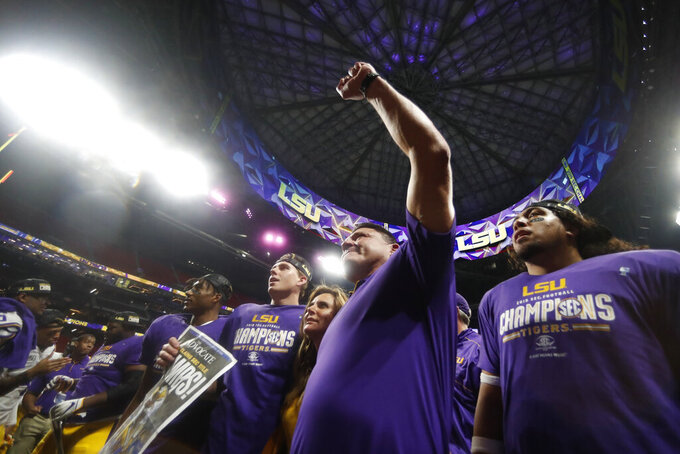 LSU head coach Ed Orgeron and team members celebrate after the Southeastern Conference championship NCAA college football game against Georgia, Saturday, Dec. 7, 2019, in Atlanta. LSU won 37-10. (AP Photo/John Bazemore)