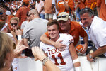 Texas quarterback Sam Ehlinger (11) celebrates with fans after defeating Oklahoma 48-45 in an NCAA college football game at the Cotton Bowl, Saturday, Oct. 6, 2018, in Dallas. (AP Photo/Cooper Neill)