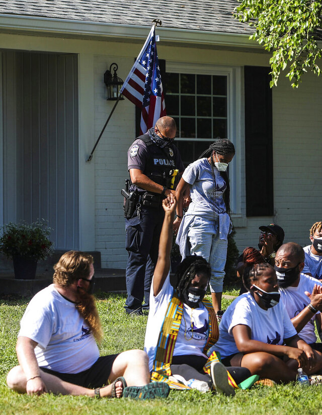 About two dozen protestors were arrested Wednesday, July 15, 2020 after sitting in the front yard of Kentucky Attorney General Daniel Cameron's home in Louisville, Kentucky, chanting Breonna Taylor's name as well as calling for justice for her killing by Louisville Metro Police Department. Cameron said he still has no timeline for when his office will conclude its investigation of the case.About two dozen protestors were arrested.  (Mary Ann Gerth/Courier Journal via AP)