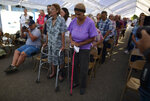 People attend an outdoor Mass under a tent set up near the Immaculate Concepcion Catholic Church, which sustained earthquake-related damaged earlier in the week, following a magnitude 5.9 quake earlier in the day in Guanica, Puerto Rico, Saturday, Jan. 11, 2020. The morning quake caused further damage along the island's southern coast, where previous recent quakes have toppled homes and schools. (AP Photo/Carlos Giusti)