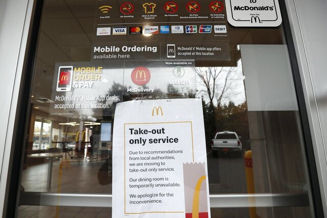 A McDonald's restaurant in Chapel Hill, N.C. displays signage informing customers of take-out service only in light of the coronavirus outbreak Tuesday, March 17, 2020. Gov. Roy Cooper earlier today mandated all bars and restaurants in North Carolina close to encourage social distancing. Takeout, delivery and drive-thru options may still be available, depending on the restaurant. (AP Photo/Gerry Broome)