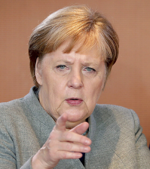 German Chancellor Angela Merkel points as she arrives for the weekly cabinet meeting at the Chancellery in Berlin, Germany, Wednesday, Dec. 18, 2019. (AP Photo/Michael Sohn)