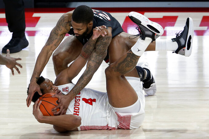 South Carolina guard Seventh Woods (23) reaches to get the ball from Houston forward Justin Gorham (4) during the second half of an NCAA college basketball game Saturday, Dec. 5, 2020, in Houston. (AP Photo/Michael Wyke)