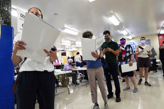 Voters wait to mark their ballots at Frank McCourt High School, in New York, Tuesday, June 22, 2021. The final votes are set to be cast Tuesday in New York's party primaries, where mayors, prosecutors, judges and city and county legislators will be on the ballot, along with other municipal offices. (AP Photo/Richard Drew)