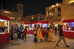 FILE - In this Nov. 7, 2018 file photo, Indians walk in the Al Seef district during the Diwali festival in Dubai, United Arab Emirates. Amid the Kashmir crisis, Gulf Arab states balance relations with Muslim-majority Pakistan, trade partner India. In the UAE Indians outnumber Emiratis three to one and bilateral trade surpassed $50 billion in 2018, making India the UAE's second-largest trade partner. (AP Photo/Kamran Jebreili, File)